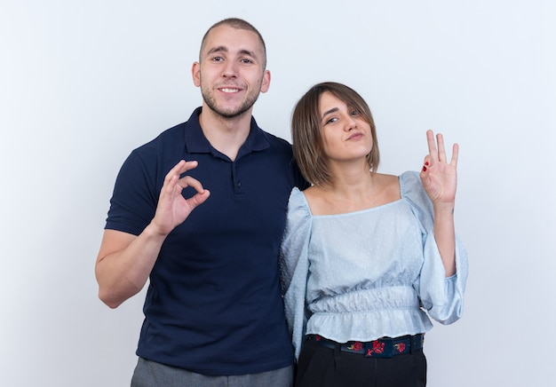Giovane bella coppia in abiti casual uomo e donna che guardano sorridenti allegramente mostrando segno ok in piedi