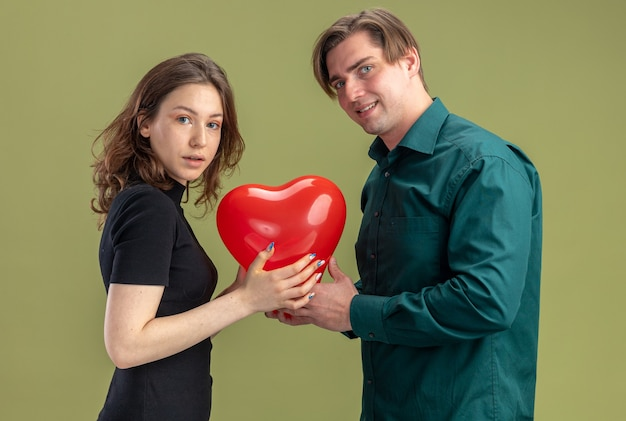 Giovane bella coppia in abiti casual uomo e donna con palloncino a forma di cuore felice innamorato insieme abbracciando per celebrare il giorno di san valentino in piedi su sfondo verde