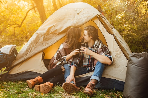 Young beautiful couple in casual dress sitting in a campsite near the tent