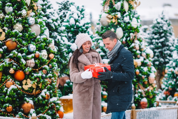 Young beautiful couple celebrating christmas in the city street and giving gift to each other