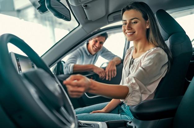 若い美しいカップルは新しい車を選びます。女性が車の中に座って、男性がドアから覗きます。購入とレンタカー。