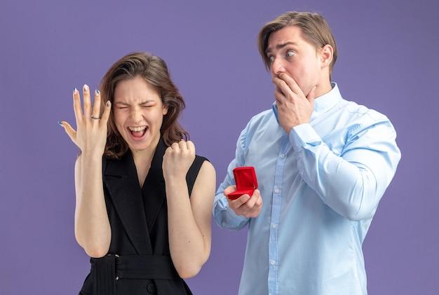 若い美しいカップルは、青い背景の上に立っている彼女の指のバレンタインデーのコンセプトに婚約指輪で彼の興奮した狂気の幸せなガールフレンドを見て赤いボックスで混乱してショックを受けた男