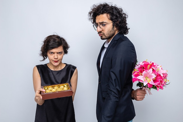 Young beautiful couple confused man hiding bouquet of flowers behind his back looking at his angry girlfriend with box of chocolates celebrating international womens day march 8