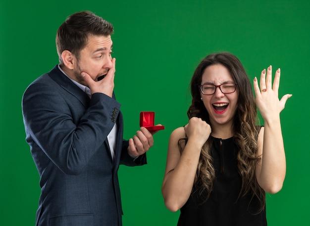 Giovane bella coppia confuso uomo con scatola rossa che fa una proposta alla sua bella ragazza eccitata che mostra l'anello di fidanzamento al dito festeggiando san valentino in piedi sul muro verde