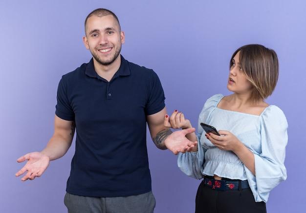 若い美しいカップルは、青い壁の上に立つ不注意な笑顔のボーイフレンドを見て、憤慨して腕を上げたスマートフォンで女性を混乱させた