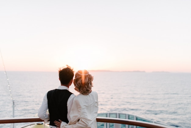 Young beautiful couple on the deck of a cruise liner in the sea