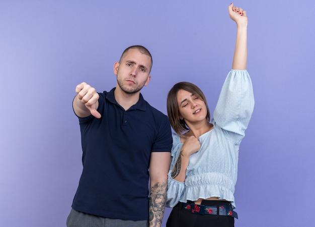 Giovane bella coppia dispiaciuto uomo che mostra i pollici in giù mentre la sua ragazza felice e allegra si diverte in piedi sul muro blu
