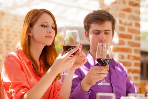レストランでワインのグラスを飲む若い美しいカップル。