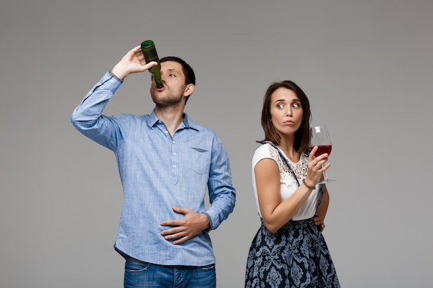 Young beautiful couple drinking wine and beer over grey wall