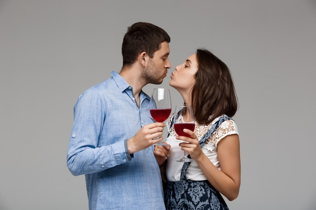 Young beautiful couple drinking wine over grey wall