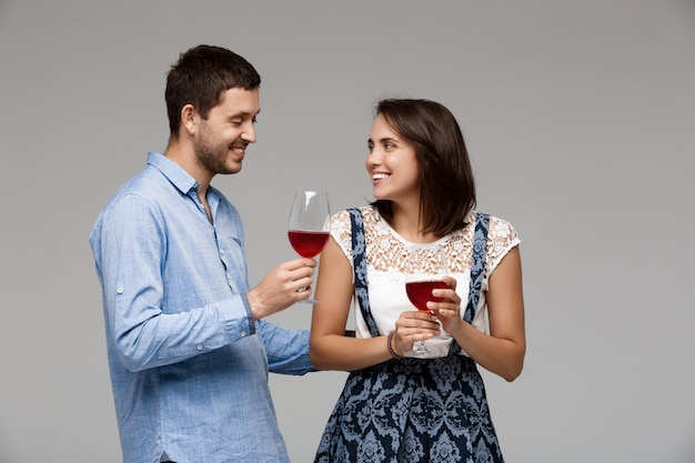 Young beautiful couple drinking wine, smiling over grey wall
