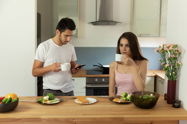 朝食に健康的な有機食品を食べる若い美しいカップル。