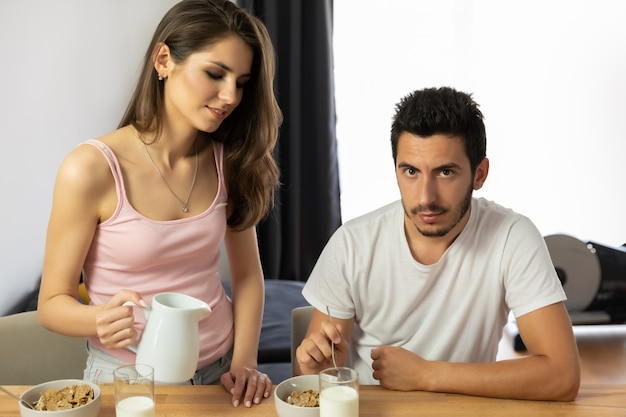 Young beautiful couple eats breakfast cereal with berries and milk.