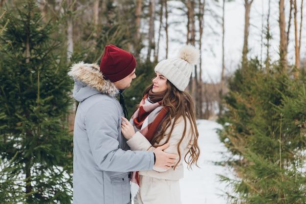젊은 아름 다운 부부는 겨울 침 엽 수 숲에서 포용. 배경에 크리스마스 트리가 있는 공원. 크리스마스 분위기. 틴팅.