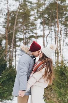 젊은 아름다운 부부는 겨울 침엽수 숲에서 포옹