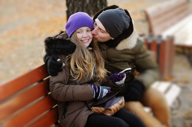 Young beautiful couple embracing on bench at the park