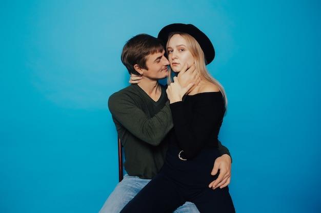 青い壁の上に座って抱き合っている若い美しいカップル。