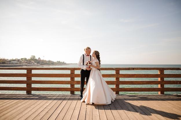 海と青空を背景に木製の橋を抱きしめる若い美しいカップル
