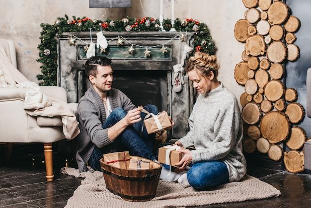 クリスマスに贈り物を交換する若い美しいカップル。クリスマスと新年のコンセプト