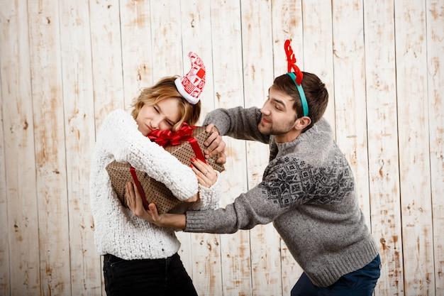 Giovani belle coppie che combattono per il regalo di natale sopra la parete di legno