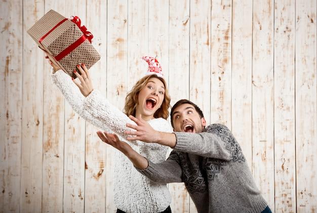 Молодая красивая пара борется за рождественский подарок над деревянной стеной