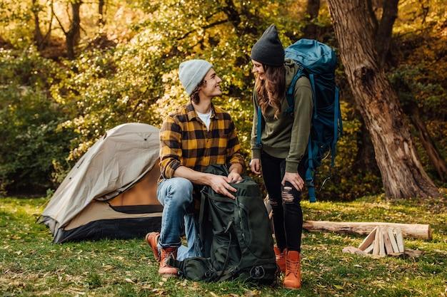 若い美しいカップルがハイキングでバックパックを集める