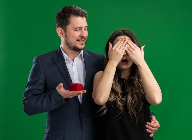 녹색 벽 위에 서있는 발렌타인 데이를 축하하는 닫힌 눈을 가진 그의 사랑스러운 흥분된 여자 친구에게 제안을 할 젊은 아름 다운 부부 잘 생긴 남자