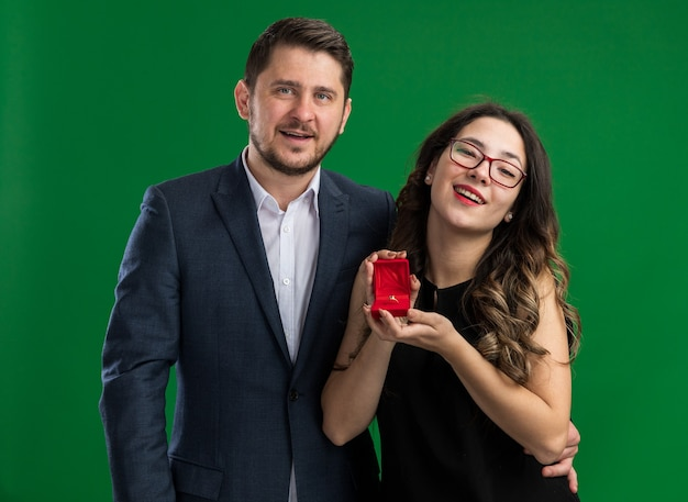 Giovane bella coppia bell'uomo che fa una proposta alla sua adorabile fidanzata con scatola rossa con anello di fidanzamento che celebra il giorno di san valentino in piedi sul muro verde