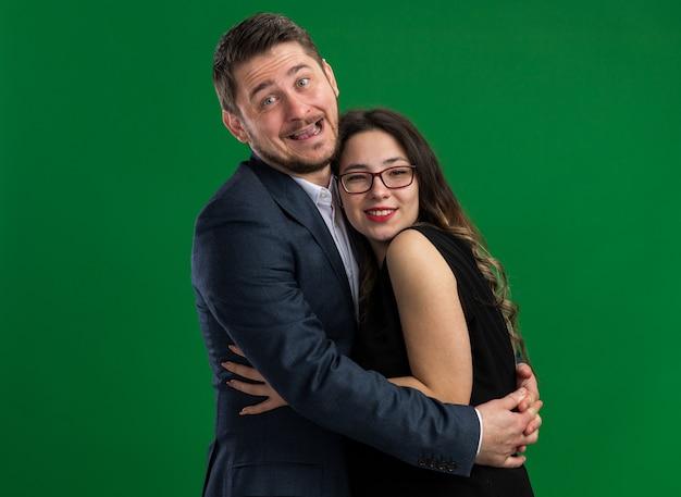젊은 아름 다운 부부 행복 하 고 쾌활 한 남자와 여자는 녹색 벽 위에 서 발렌타인 데이를 함께 축하 사랑에 행복을 포용