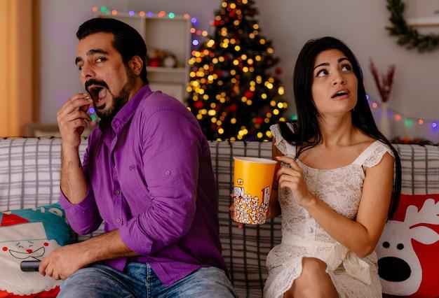 Giovane e bella coppia felice uomo allegro e donna perplessa con secchio di popcorn guardando la tv insieme nella stanza decorata con albero di natale nel muro