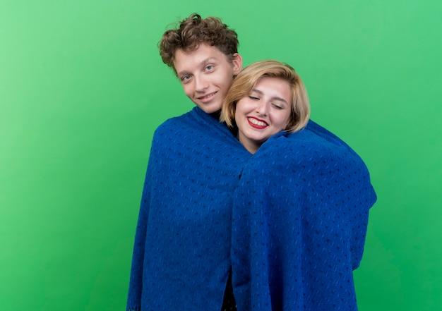 Giovane bella coppia felice in amore uomo che copre la sua ragazza in plaid in piedi sopra la parete verde