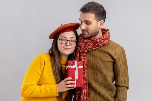 젊은 아름 다운 부부 행복 한 남자와 베레모 웃는 여자 함께 사랑에 행복을 들고 흰 벽 위에 서있는 발렌타인 데이를 축하