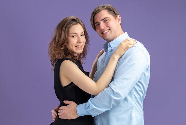 젊은 아름 다운 부부 행복 한 남자와 여자는 파란색 벽 위에 서있는 발렌타인 데이를 축하 사랑에 유쾌하게 행복 미소를 포용