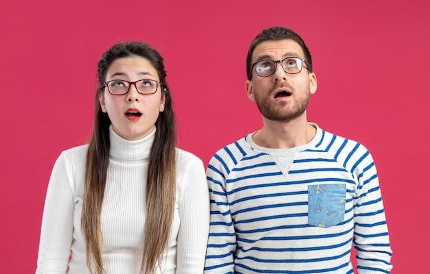 ピンクの壁の上に立っている幸せと驚きを祝うバレンタインデーのコンセプトを見上げて眼鏡をかけてカジュアルな服を着た若い美しいカップル幸せな男と女
