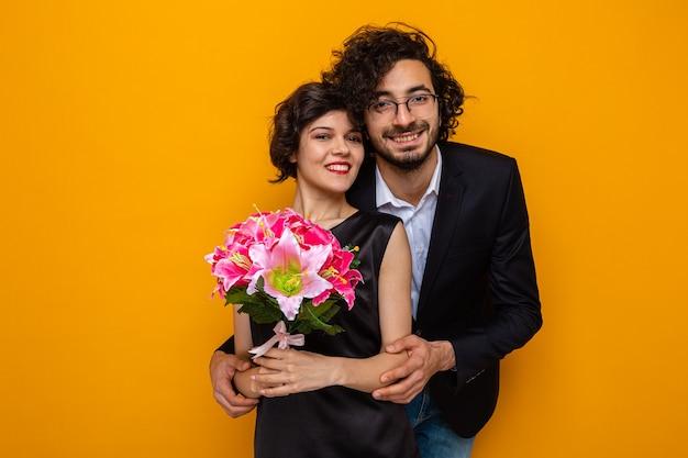 Молодая красивая пара, счастливый мужчина и женщина с букетом цветов, весело улыбаясь, обнимая счастливой в любви, празднует валентинку