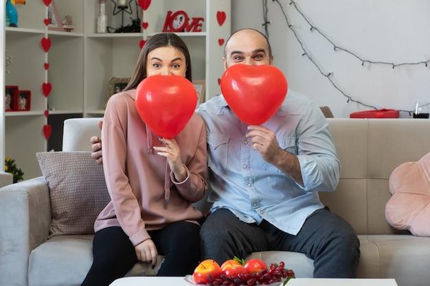 笑顔のハート型の風船と若い美しいカップル幸せな男と女