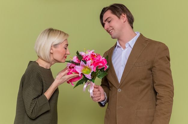 녹색 벽 위에 서있는 국제 여성의 날을 축하하는 그의 사랑스러운 여자 친구에게 꽃의 꽃다발을주는 젊은 아름 다운 부부 행복한 사람