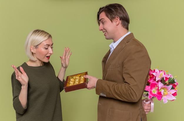 Молодая красивая пара счастливый человек дарит коробку шоколадных конфет и букет цветов своей удивленной подруге, празднующей международный женский день, стоя над зеленой стеной