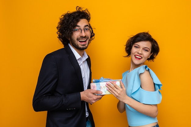 オレンジ色の背景の上に立って国際女性の日3月8日を祝う彼の幸せで驚いたガールフレンドにプレゼントを与える若い美しいカップル幸せな男