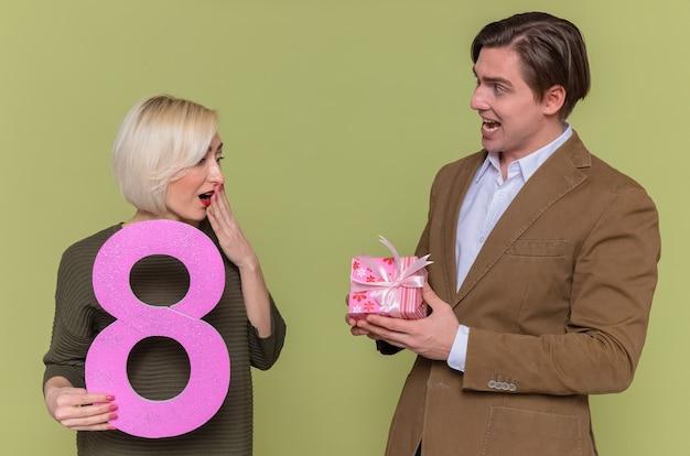 그의 놀란 여자 친구에게 선물을주는 젊은 아름 다운 부부 행복한 사람