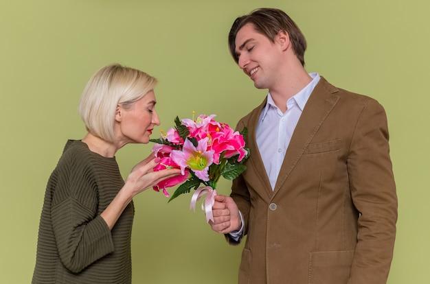 Giovane bella coppia uomo felice che dà un mazzo di fiori alla sua adorabile ragazza che celebra la giornata internazionale della donna in piedi sopra la parete verde