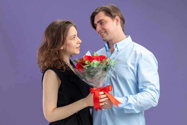 Young beautiful couple happy man giving a bouquet of red roses to his smiling lovely girlfriend celebrating valentines day standing over blue wall
