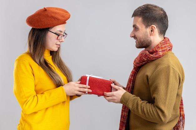Giovane bella coppia uomo felice che dà un regalo per la sua ragazza sorridente in berretto felice innamorato insieme che celebra il giorno di san valentino in piedi sul muro bianco