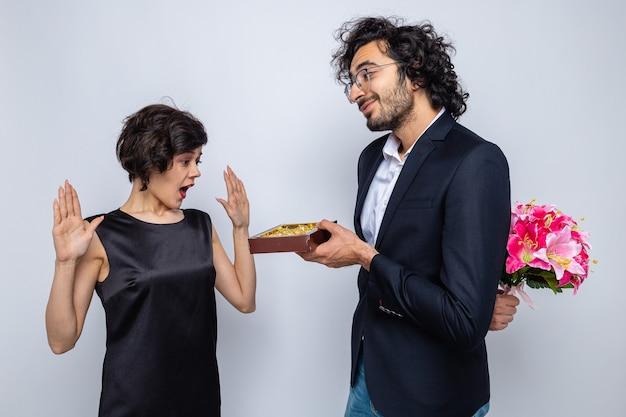 Молодая красивая пара счастливый человек прячет букет цветов за спиной, давая коробку конфет своей удивленной подруге, празднующей международный женский день 8 марта