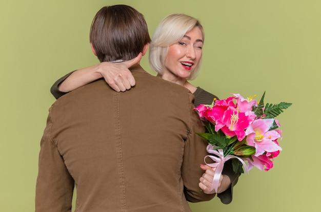 Giovane bella coppia uomo felice che abbraccia la sua adorabile fidanzata con bouquet di fiori sorridente e ammiccante che mostra pollice in su per celebrare la giornata internazionale della donna in piedi sopra la parete verde