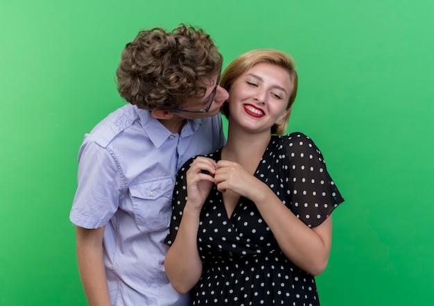 녹색 벽 위에 서 그의 사랑하는 여자 친구를 키스하는 젊은 아름 다운 부부 행복한 사람