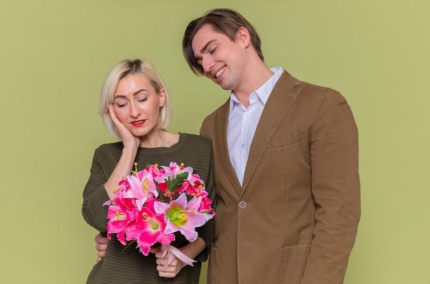 Giovane bella coppia uomo felice guardando la sua adorabile ragazza con bouquet di fiori che celebra la giornata internazionale della donna in piedi sopra la parete verde