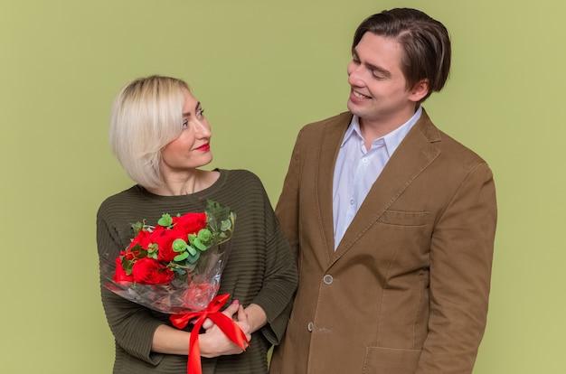 Uomo felice delle giovani belle coppie che esamina la sua amica adorabile con il mazzo delle rose rosse che celebra la giornata internazionale della donna in piedi sopra la parete verde