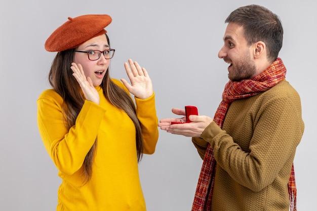 白い背景の上に立っているバレンタインデーの間にベレー帽の彼の混乱したガールフレンドに赤いボックスの婚約指輪でプロポーズをしている若い美しいカップル幸せな男
