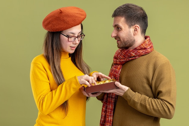 緑の背景の上に立っているバレンタインデーを祝うベレー帽で彼の笑顔の素敵なガールフレンドにチョコレート菓子を提供する若い美しいカップル幸せな男